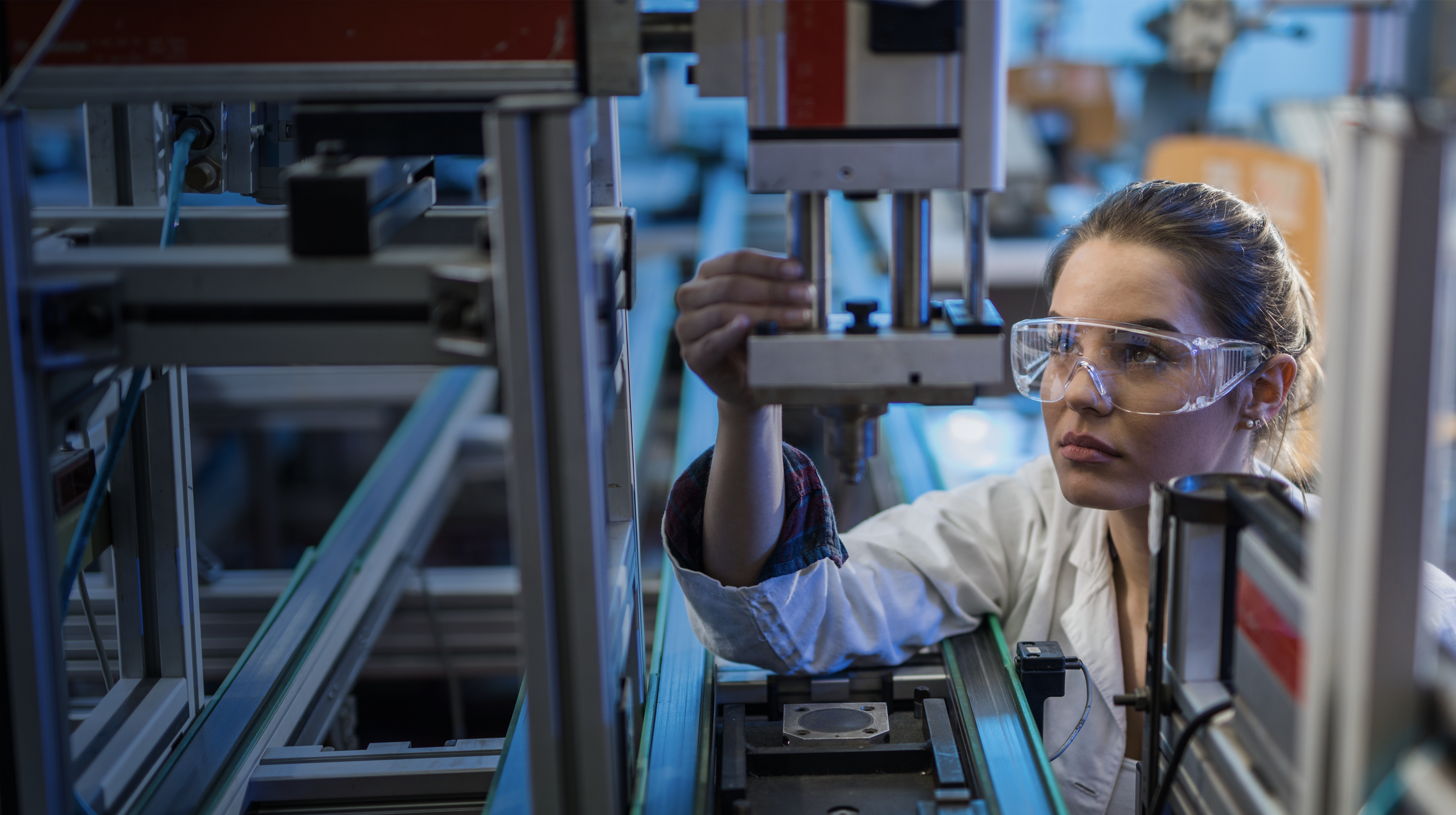 Female engineer examining machine part on a production line