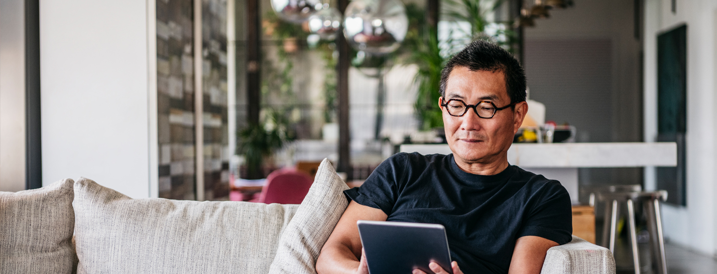 Man in glasses sat down reading from tablet