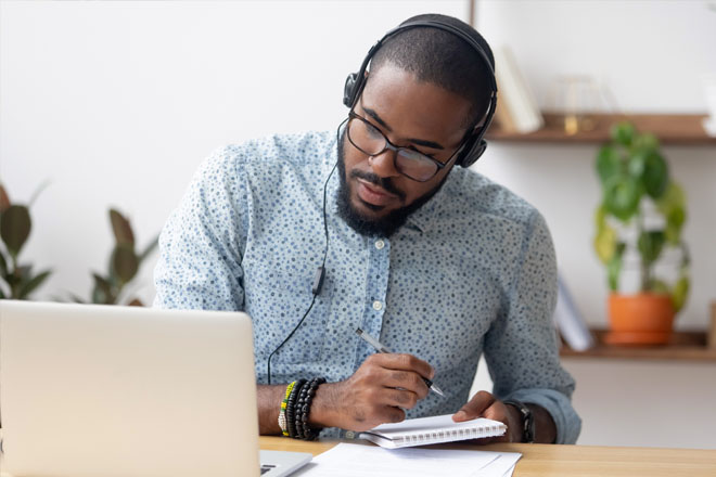 Man sat down working in office writing on pad