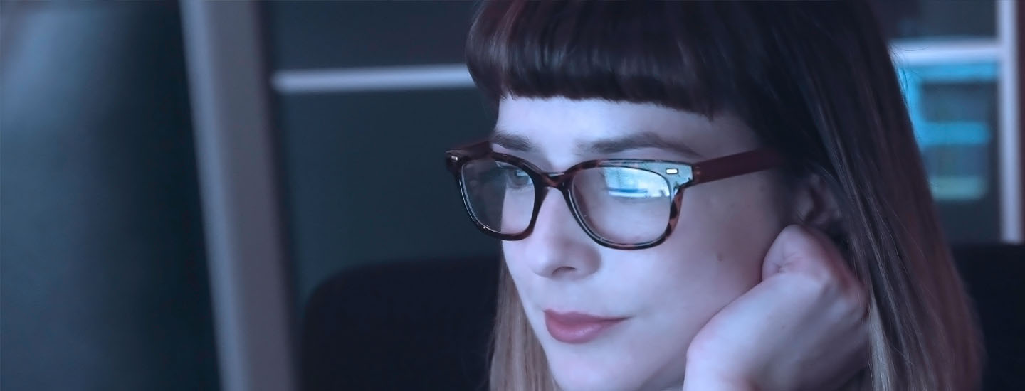Woman sat at computer reading emails with screen relection on glasses