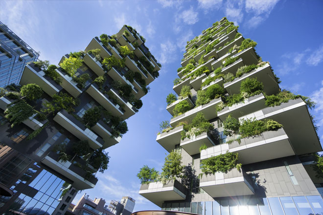 Shot looking upwards towards leafy buildings Bosco Verticale in Milan Italy