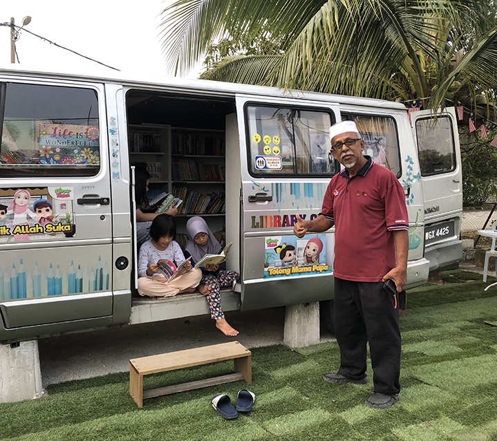 Malaysian gentleman giving thumbs up to camera with two children reading in mobile library