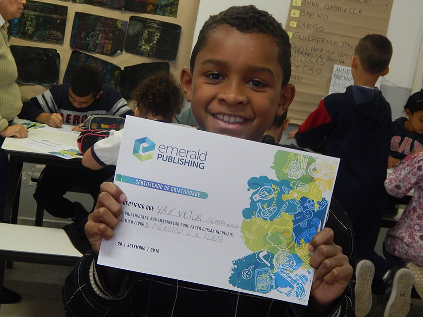 South American child displaying an Emerald Certificate