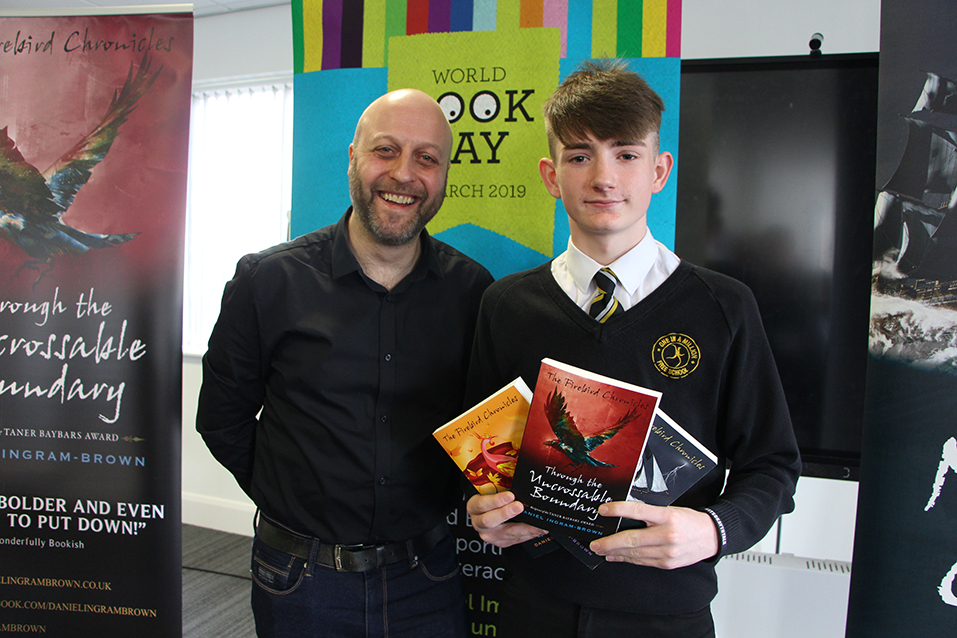 Student displaying 3 books posing with the author