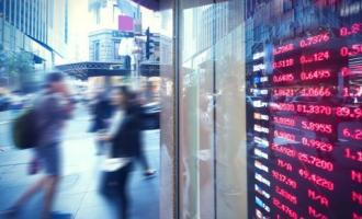Blurred image of people walking past digital sign featuring exchange rates