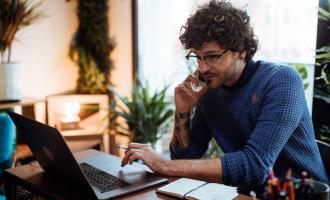 Man sat in modern cosy office on phone whilst working on laptop at desk