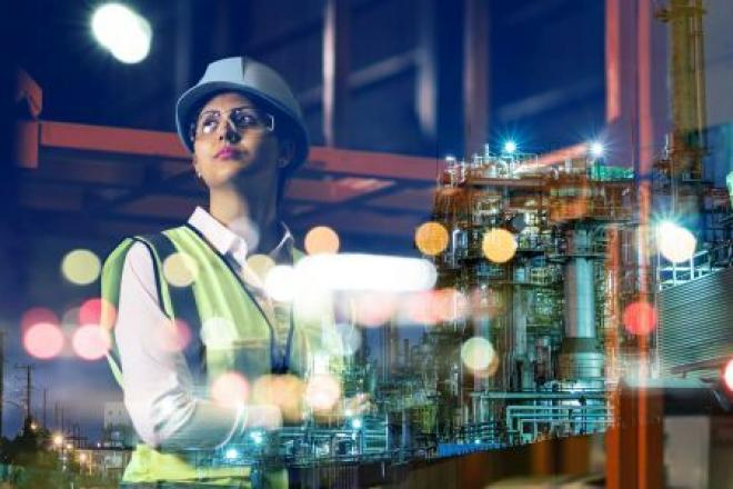 Woman site engineer wearing hard hat and high vis jacket looking over a city at night